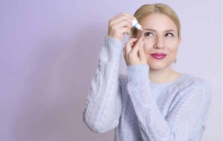 woman using eye drops to treat pink eye