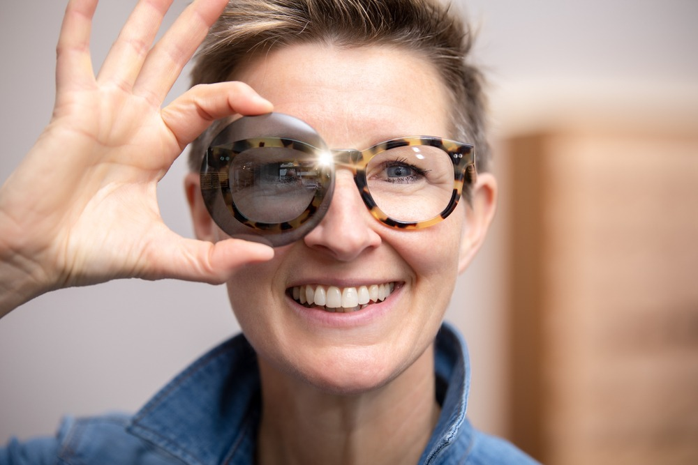 woman holding tinted lens in front of her glasses