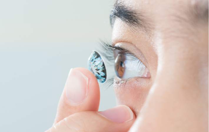 close-up of someone putting in a blue coloured contact lens