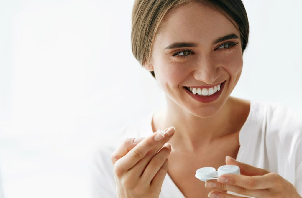woman smiling as she is putting in her contact lenses with the proper care