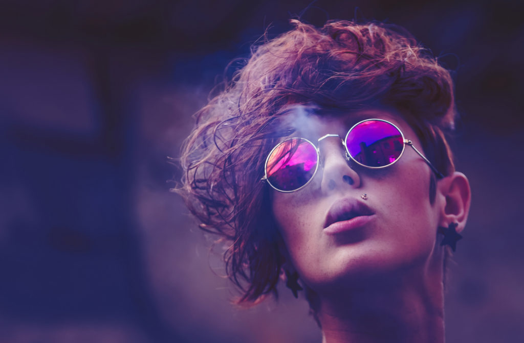 woman with short curly hair and round polarized glasses with the city skyline reflecting in her glasses