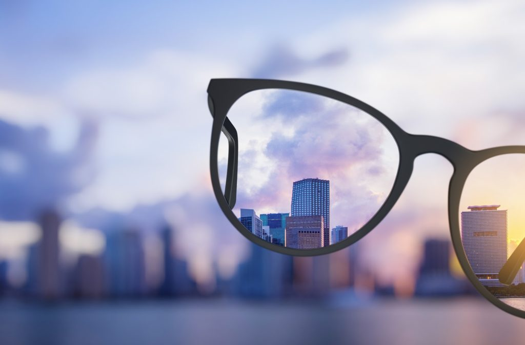 Blurred city scape at sunset with glasses in the forefront and the scene clear through the glasses' lens