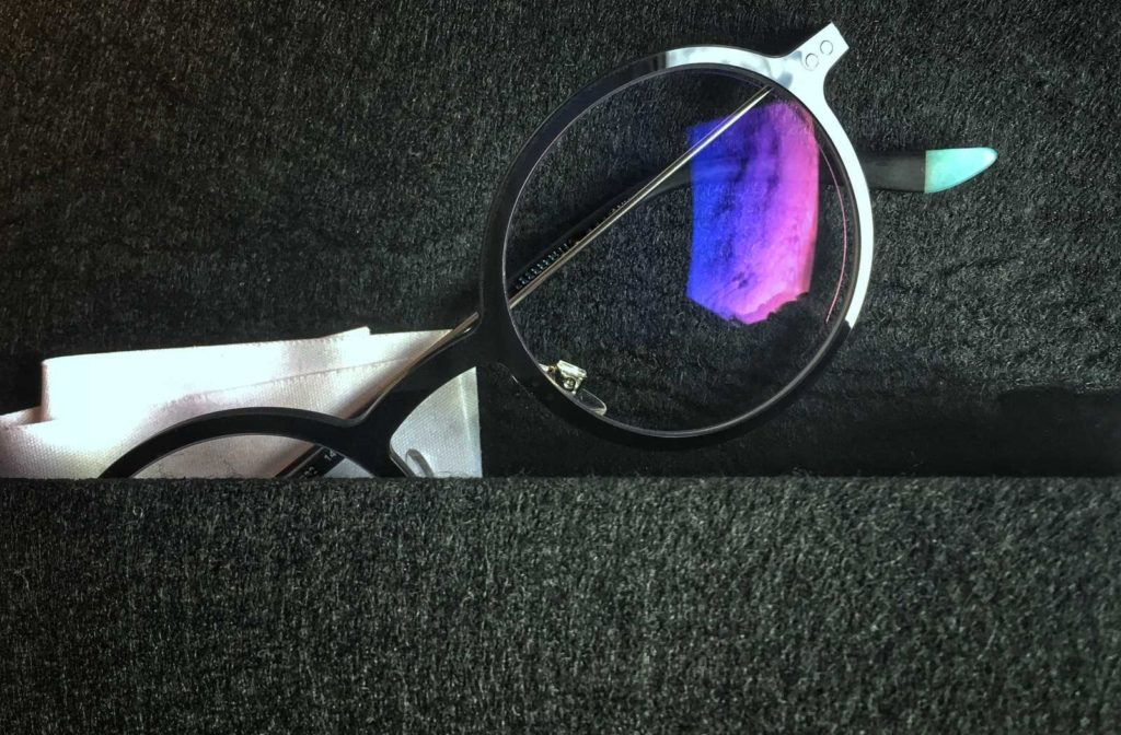 glasses on black wool with lenses reflecting blue, indigo, and violet light off the upper surface
