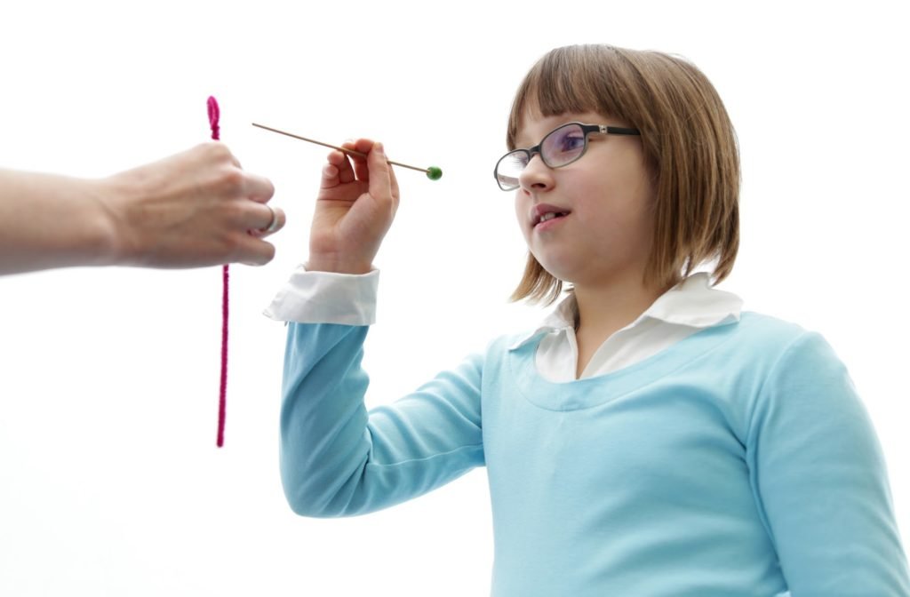 A little girl performing eye vision therapy to prevent lazy eye