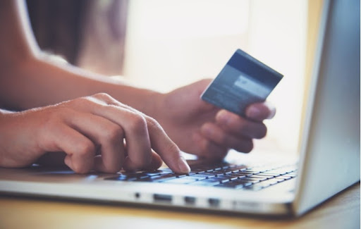 A person's hands holding a credit card while using a laptop to online shop for contact lenses