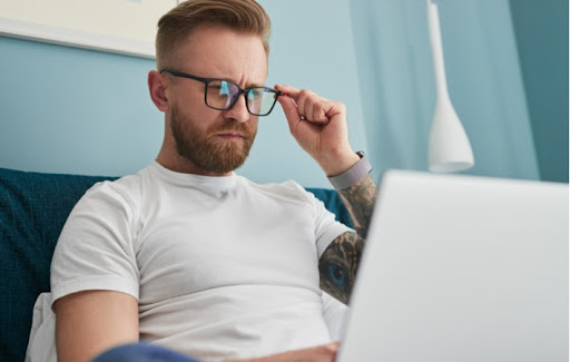 A man adjusting to new glasses squinting slightly while he looks at his laptop